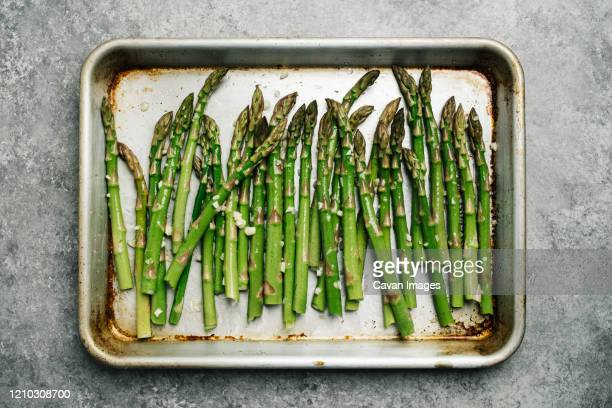 oiled asparagus on a baking sheet - asparagus stock pictures, royalty-free photos & images
