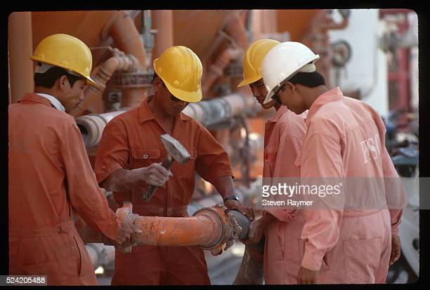 Oilfield workers for Mobil Oil work on a pipe in Vung Tau, Vietnam, at a support station for offshore oil platforms in the South China Sea.