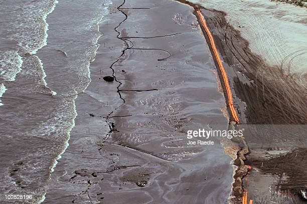Oily absorbent material along with containment booms are seen placed on the beach as efforts to clean the beach from effects of the Deepwater Horizon...