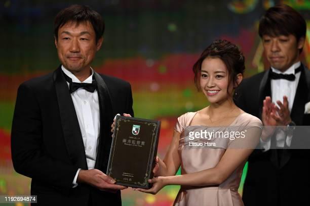 Oita Trinita head coach Tomohiro Katanosaka receives Manager of the Year award from Emiri Nakagawa during the J.League Awards on December 08, 2019 in...