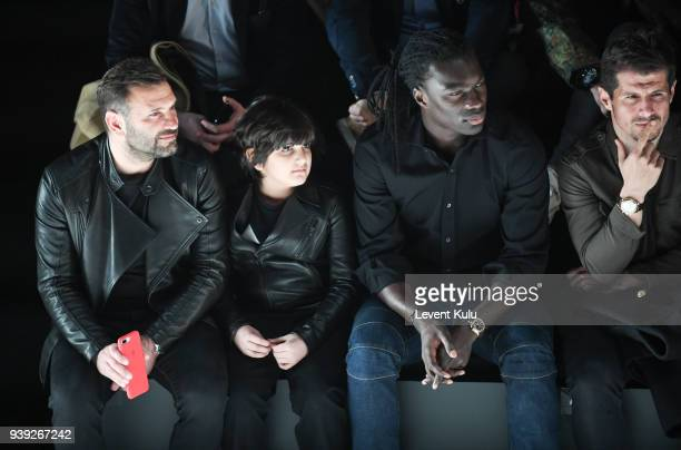 Okan Buruk with and son Bafetimbi Gomis and Emre Belezoglu attend the St Nian show during Mercedes Benz Fashion Week Istanbul at Zorlu Performance...