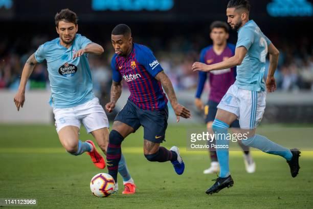 Okay Yokuslu of RC Celta competes for the ball with Malcom of Barcelona during the La Liga match between RC Celta de Vigo and FC Barcelona at...