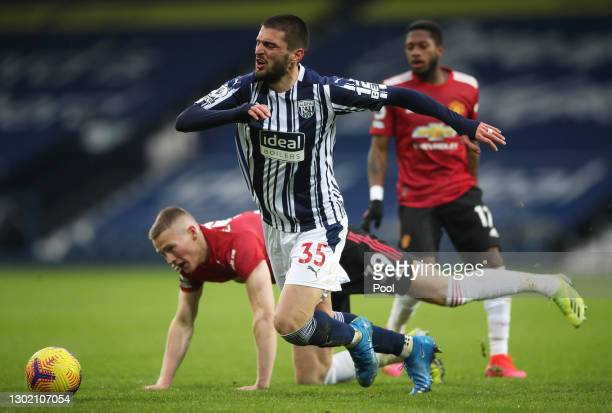 Okay Yokuslu of West Bromwich Albion is challenged by Scott McTominay of Manchester United during the Premier League match between West Bromwich...