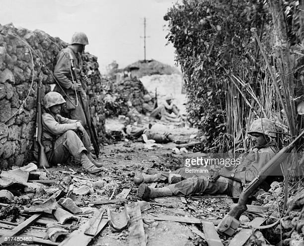 Okinawa: In Suburbs Of Naha--Tired Sixth Marine Division Leathernecks, fighting the stubborn Japs for the possession of Naha on Okinawa Island, rest...