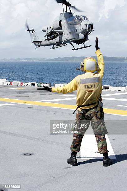 Okinawa, Japan, September 23, 2008 - Airman uses hand and arm signals to direct an AH-1W Super Cobra onto the flight deck of USS Essex.