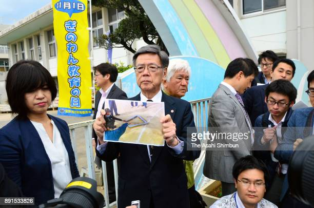 Okinawa Prefecture Governor Takeshi Onaga shows reporters an image of the window frame that fell from a US CH53 helicopter at the Futenma Daini...