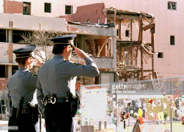 Oklahoma City police officers salute 19 April during a moment of silence at a memorial service held on the first anniversary of the bombing of the...
