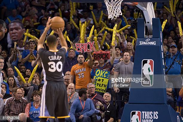 Oklahoma City Thunder fans try to distract Stephen Curry of the Golden State Warriors as he shoots a free throw during the third period of a NBA game...