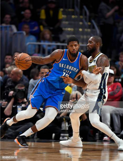 Oklahoma City Thunder forward Paul George drives on Denver Nuggets guard Will Barton during the first quarter on October 10 2017 in Denver Colorado...