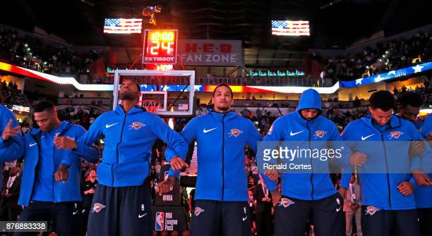 Oklahoma City Thunder join arms during the National Anthem before the start of their game against the San Antonio Spurs at ATT Center on November 17...