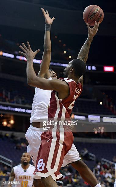 Oklahoma guard Cameron Clark puts up a shot and scores over George Mason guard Marquise Moore in the first half an NCAA basketball game at the BBT...