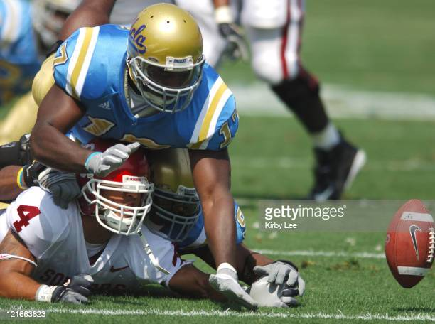 Oklahoma receiver Travis Wilson battles with UCLA defensive end Justin Hickman and linebacker Justin London for a fumble during 41-24 loss at the...