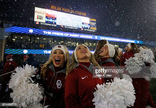 Oklahoma Sooner cheerleaders eat snowflakes during a snow equal before the game against the West Virginia Mountaineers on November 19 2016 at...