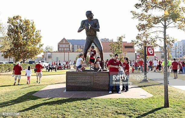 Oklahoma Sooners fans wait on the statue of Heisman winner Sam Bradford before the game against the Kansas Jayhawks October 29 2016 at Gaylord...