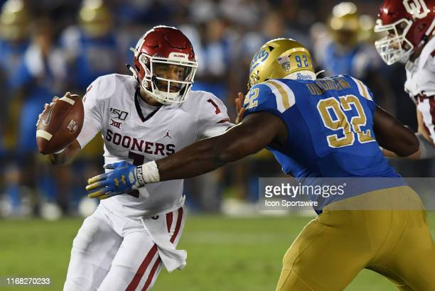 Oklahoma Sooners Jalen Hurts runs for a first down and tries to avoid being tackled by UCLA Bruins Jason Harris in the second half of a college...