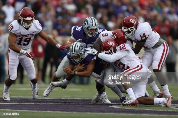 Oklahoma Sooners linebacker Kenneth Murray and defensive back Will Johnson tackle Kansas State Wildcats quarterback Alex Delton after a short gain in...