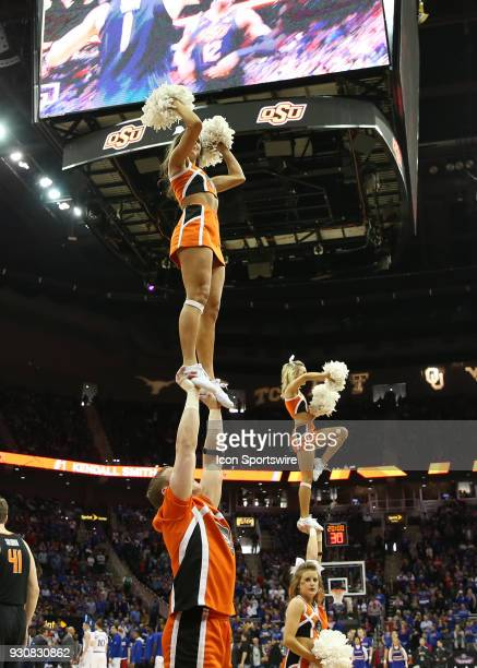 Oklahoma State cheerleaders perform high above the floor in the first half of a quarterfinal game in the Big 12 Basketball Championship between the...
