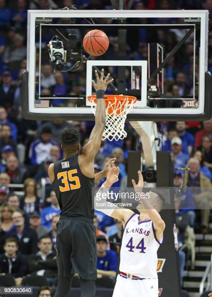 Oklahoma State Cowboys forward Yankuba Sima goes high over Kansas Jayhawks forward Mitch Lightfoot for an easy basket in the first half of a...