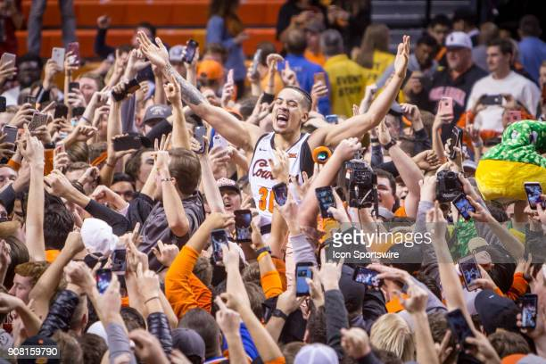Oklahoma State Cowboys guard Jeffrey Carroll celebrates with students after the crowd rushes the court after following the college Big 12 conference...