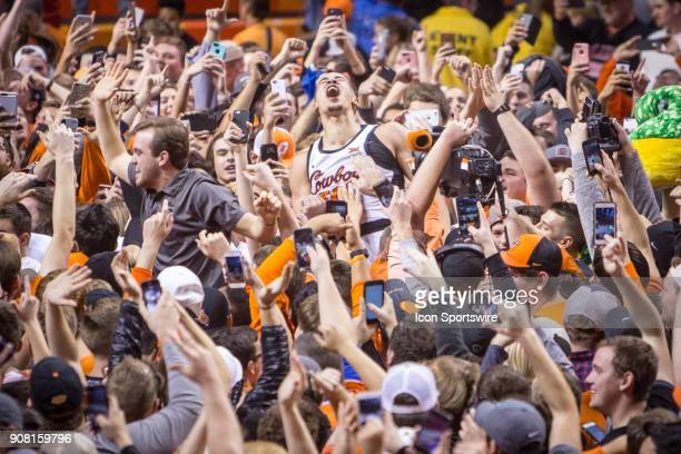 Oklahoma State Cowboys guard Jeffrey Carroll celebrates with students after the crowd rushes the court following the college Big 12 conference mens...
