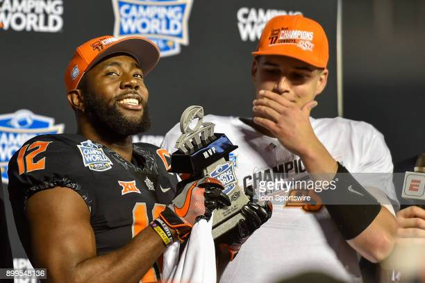 Oklahoma State Cowboys linebacker Kirk Tucker holds up the MVP trophy given to Oklahoma State Cowboys quarterback Mason Rudolph on his right during...