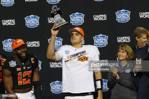 Oklahoma State Cowboys quarterback Mason Rudolph holds up the MVP trophy after winning the Camping World Bowl between the Virginia Tech Hokies and...