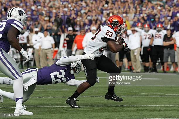 Oklahoma State Cowboys running back Rennie Childs breaks a tackle by Kansas State Wildcats defensive back Dante Barnett during the Oklahoma State...