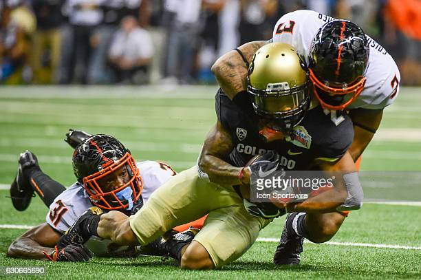 Oklahoma State Cowboys safety Kenneth EdisonMcGruder and Oklahoma State Cowboys safety Tre Flowers tackle Colorado Buffaloes wide receiver Devin Ross...