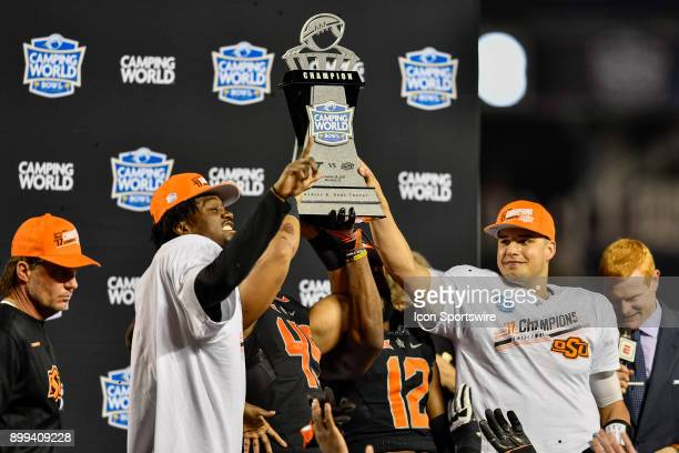 Oklahoma State Cowboys safety Tre Flowers and Oklahoma State Cowboys quarterback Mason Rudolph hold up the trophy with teammates during the champions...