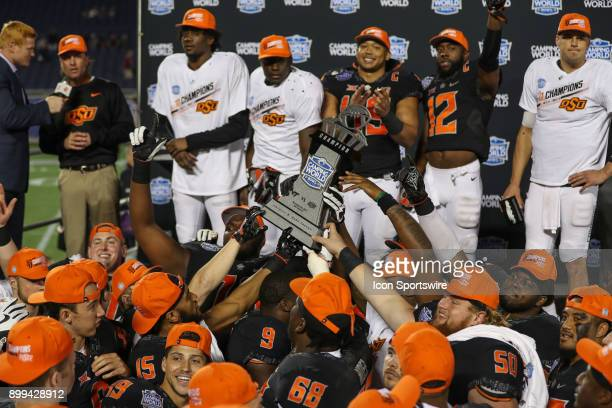 Oklahoma State players hold up the trophy after winning the Camping World Bowl between the Virginia Tech Hokies and the Oklahoma State Cowboys on...