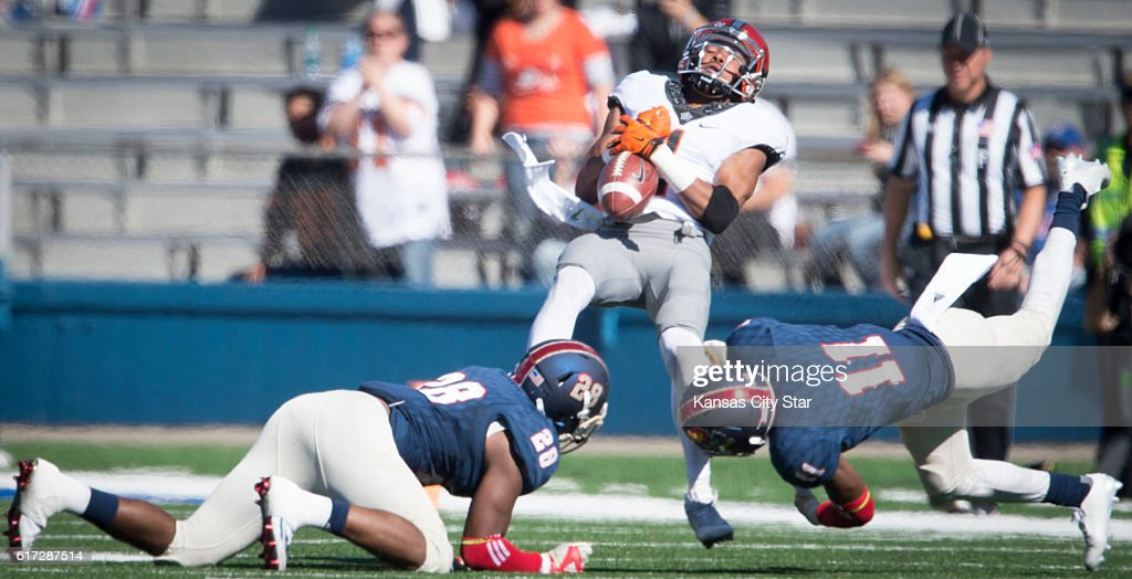 Oklahoma State wide receiver Jalen McCleskey (1) hangs onto the ball as he is tackled by Kansas linebackers Courtney Arnick (28) and Mike Lee (11) in the first quarter at Memorial Stadium in Lawrence, Kan., on Saturday, Oct. 22, 2016. Oklahoma State won, 44-20.