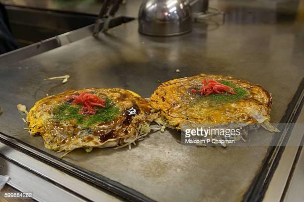 okonomiyaki, japanese savoury pancakes, hiroshima, japan - hiroshima city stock photos and pictures