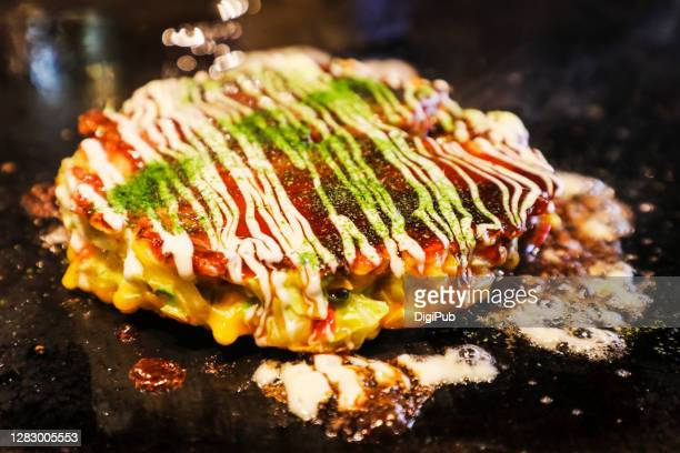 okonomiyaki on griddle - okonomiyaki stock pictures, royalty-free photos & images