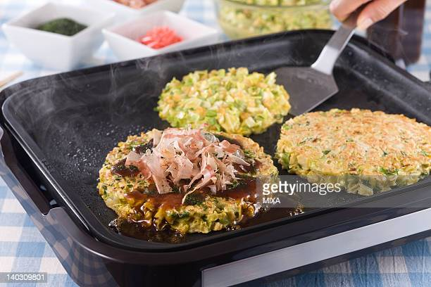 okonomiyaki on hot plate - okonomiyaki stock pictures, royalty-free photos & images