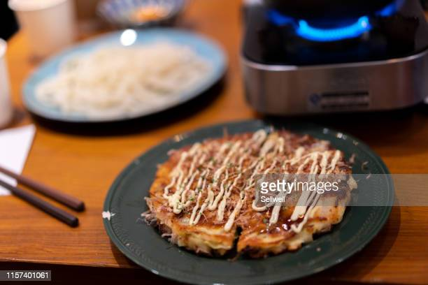 okonomiyaki on the table - okonomiyaki stock pictures, royalty-free photos & images