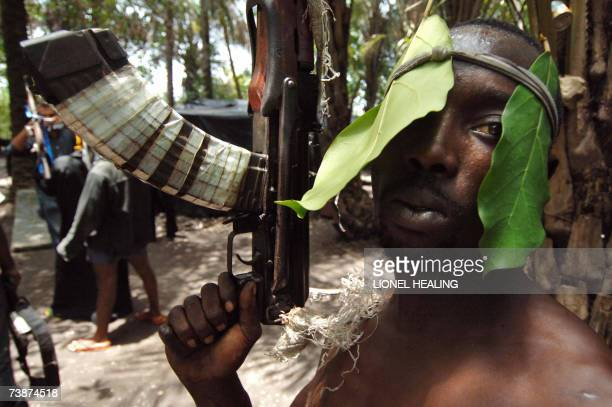 An Ateke Tom militants stands with his guns in his camp 13 April 2007 in Okrika Rivers State Ateke Tom is the leader of the Niger Delta Vigilante an...