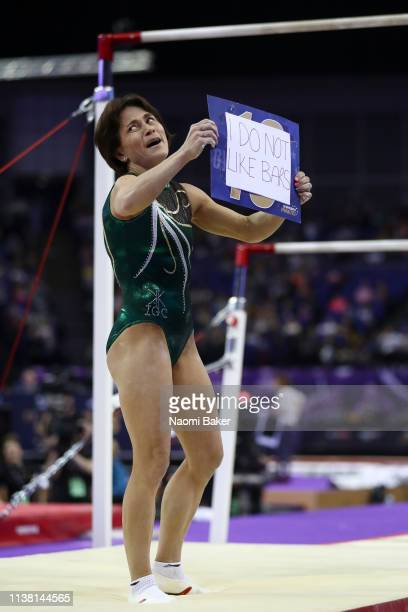 Oksana Chusovitina holds up a sign reading ' i do not like bars' after performing on the uneven bars during the Superstars of Gymnastics at The O2...