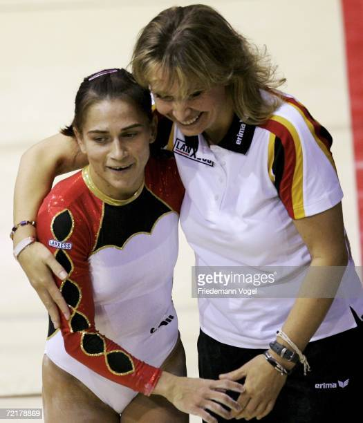 Oksana Chusovitina of Germany and her coach Jhana Poljakova celebrate after the uneven bars in the womens qualification during the World Artistic...