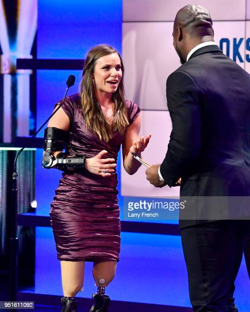 Oksana Masters accepts the Female Paralympic Athlete of the Games award with Vernon Davis during the Team USA Awards at the Duke Ellington School of...