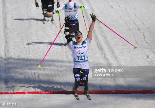 Oksana Masters of the US celebrates her victory after crossing the finish line in the women's 11km sprint sitting crosscountry skiing final event of...
