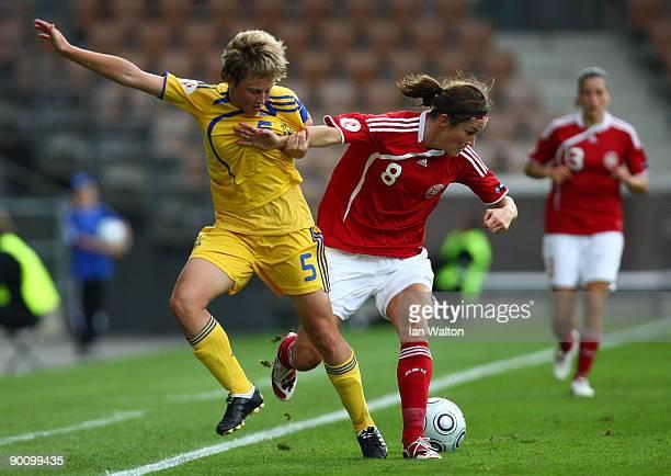 Oksana Yakovyshn of Ukraine tries to tackle Julie Bukh of Denmark during the UEFA Women's Euro 2009 group A preliminary match between Ukraine and...