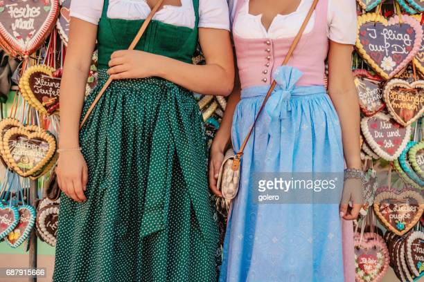 oktoberfest dirndls in front of gingerbread hearts - traditional clothing stock pictures, royalty-free photos & images