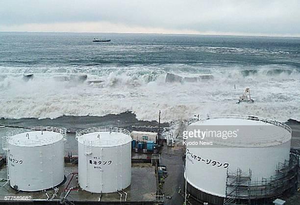 Okuma Japan Handout photo shows tsunami triggered by a powerful earthquake approaching fuel oil tanks of the No 5 reactor at the Fukushima Daiichi...