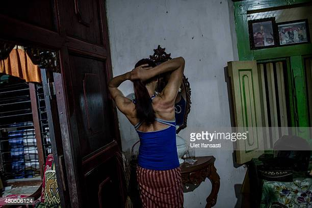 Oky a member of a Pesantren boarding school AlFatah for transgender people known as 'waria' looking at the mirror as attend during Ramadan on July 12...