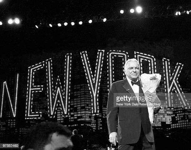 Ol' Blue Eyes Frank Sinatra clutches bouquet of flowers handed to him by an admirer following show at Radio City Music Hall