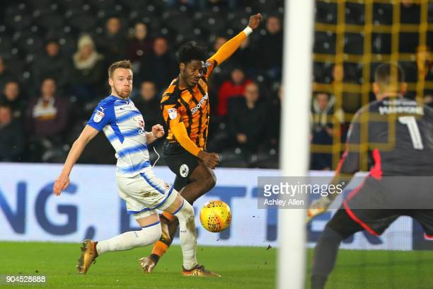 Ola Aina of Hull City crosses the ball into the box as Chris Gunter of Reading attempts to block it during the Sky Bet Championship match between...