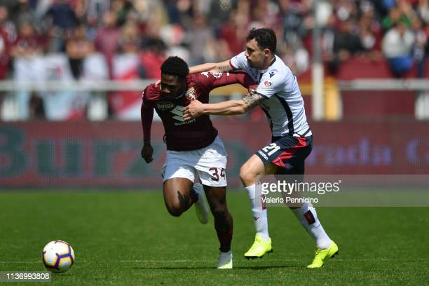 Ola Aina of Torino FC is challenged by Artur Ionita of Cagliari during the Serie A match between Torino FC and Cagliari at Stadio Olimpico di Torino...