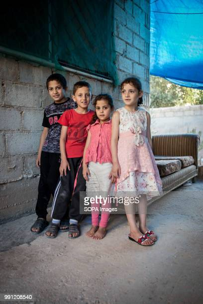 Ola and her siblings stand outside their house in Zaatari There are about 14 million Syrian refugees in Jordan and only 20 percent are living in the...