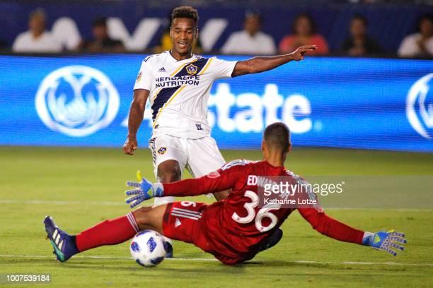 Ola Kamara of the Los Angeles Galaxy kicks the ball as Earl Edwards Jr #6 of the Orlando City SC dives for the save at StubHub Center on July 29 2018...