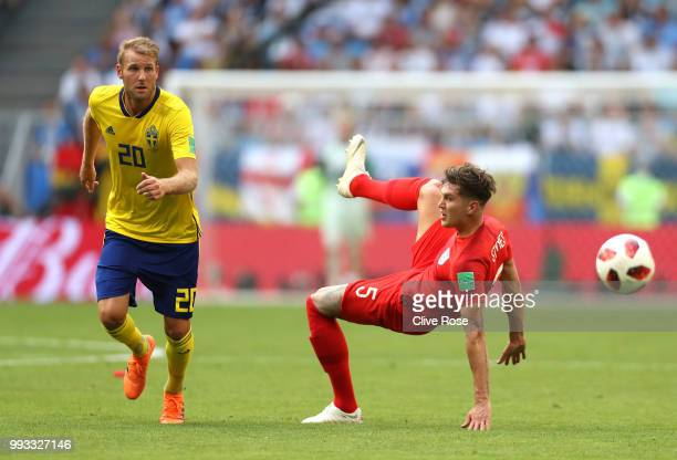 Ola Toivonen of Sweden and John Stones of England compete for the ball during the 2018 FIFA World Cup Russia Quarter Final match between Sweden and...
